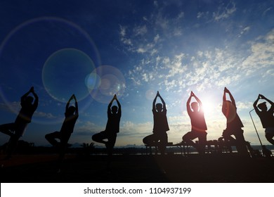 Silhouette of men train Yoga on lawn yard along River Mountain during SunRise over Nice Blue Sky as backgrounds, Group of Students learn practice Lotus Pose in sunset, copy space for text logo