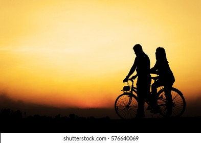 silhouette men and women are riding bikes together.In love