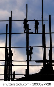 Silhouette of men working on a Bamboo Scaffolding.