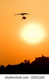 Silhouette of microlight aircraft flying over the orange sunset.
