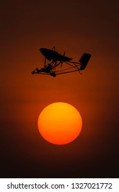Silhouette microlight aircraft with sunset background.