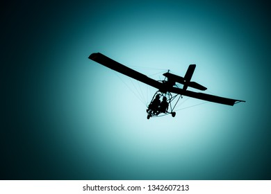 Silhouette of microlight flying.