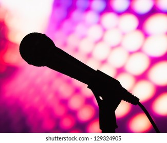 silhouette of microphone against purple disco background