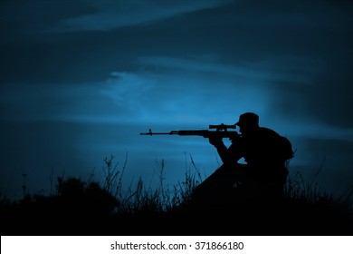 Silhouette of military sniper with weapons at night. night vision concept