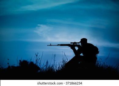 Silhouette of military sniper with weapons at night. shot, holding gun, blue colorful sky, background