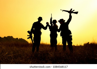 Silhouette of military soldier holding weapons overhead after get victory of war at sunset.