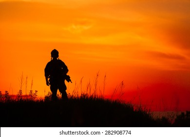 Silhouette of military soldier or officer with weapons at sunset. shot, holding gun, colorful sky, background