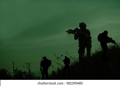 Silhouette of military soldier or officer with weapons at night. shot, holding gun, green colorful sky, background