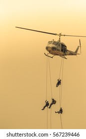 Silhouette of military soldiers in action rappelling climb down from helicopter with military mission secure training.