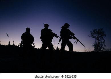 Silhouette of military soldiers with weapons at night. shot, holding gun, colorful sky. military concept.