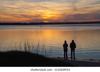 A silhouette of a mindful couple standing on a beach together by the water contemplatively watching a colorful sunset over the water