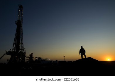 Silhouette of a mining work with a drilling rig in the background