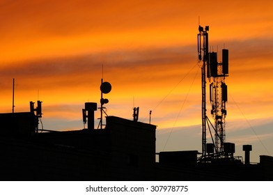 Silhouette of mobile communication antennas in an orange sunset