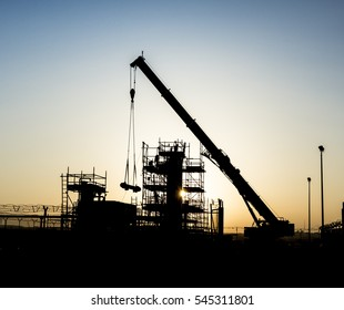 Silhouette of mobile crane working in gas plant of oilfield