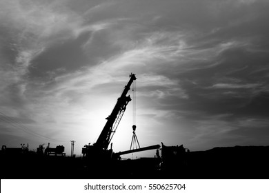 Silhouette of mobile crane working in gas plant of oilfield - black and white