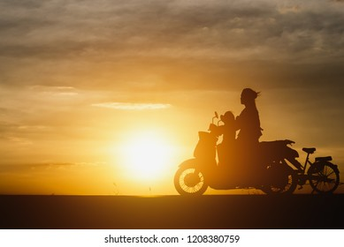Silhouette of Mom and baby are riding motorcycles.