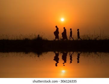 Silhouette of monk walk on the field  , Thailand