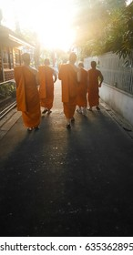 Silhouette monk walking with sunset light. Shoot in blur effect.