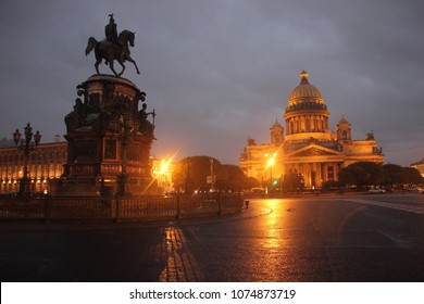 The silhouette of monument statue of Czar Nicholas 1 with the illuminated Saint Isaac Cathedral in background at Saint Petersburg, Russia.