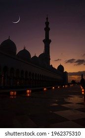 A silhouette of a mosque against dimly lit sky with Eid crescent. Islamic Eid or Ramadan background.