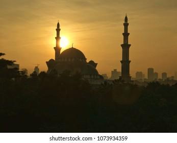 Silhouette Mosque and Kuala Lumpur city skyline during sunrise