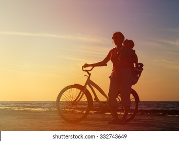 Silhouette of mother and baby biking at sunset beach