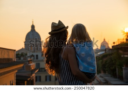 Silhouette of mother and baby girl looking on rooftops of rome on sunset. rear view