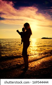 Silhouette of mother and baby on the beach.Shoot in the back light technique