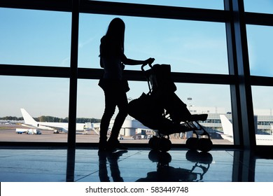 silhouette of a mother with baby in stroller in an airport waiting hall. family concept