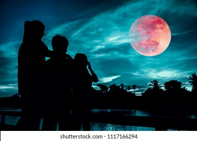 Silhouette of mother and children looking at red super moon or blood moon on colorful sky with cloud. Serenity nature background. Happy family spending time together.