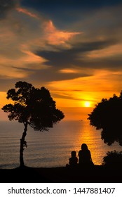 Silhouette of mother and daughter enjoying the sun set on cliff