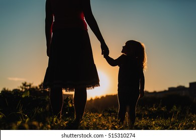 silhouette of mother and daughter holding hands at sunset