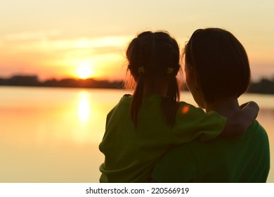 silhouette of mother and daughter on sunset background