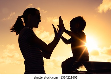 silhouette of mother and her little son doing high five playing together,  happy parenting