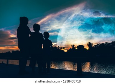 Silhouette of mother with her son and daughter looking at supermoon on colorful sky . Beautiful nature background. Spending time outdoors, cozy mood. The moon taken with my camera.