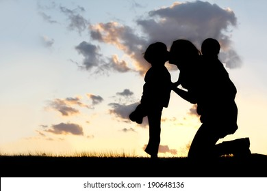 the Silhouette of a mother and her two young children; a little boy and his baby brother are playing outside at sunset, hugging and kissing on a summer day.