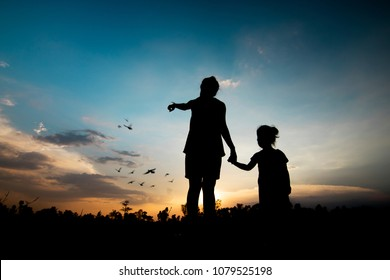 silhouette mother holding daughther looking bird flying, concept as freedom, hope and teaching to success