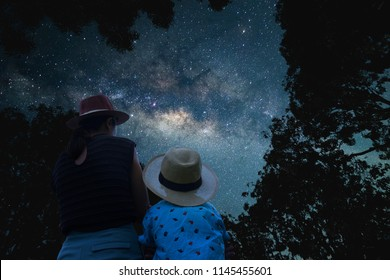 Silhouette Mother and son Asian couple standing under the shadow of a big tree. Looking at the stars and the Milky Way on the romantic and happy night. Long exposure, with grain.