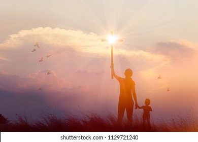 Silhouette of mother and son christian prayers raising cross while praying to the Jesus on sunset background, worship concept