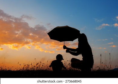 Silhouette of a mother and son holding umbrella and playing outdoors at sunset