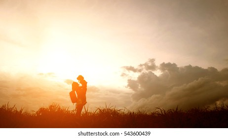 Silhouette of A mother and son playing outdoors at sunset.