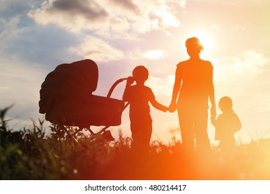 Silhouette of mother with three kids walking at sunset