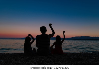 Silhouette of a mother with two daughters sitting on a beach after sunset, throwing rocks in the ocean.