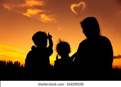 Silhouette of mother and two kids sitting and looking sky at sunset. Little boy point to heart-shape clouds. Colorful sky background orange and gold colors sunset sky. Friendly family.
