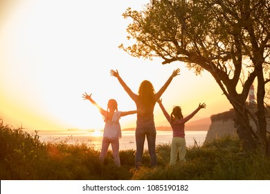 Silhouette of mother with two little daughters looking away into the sunset and water