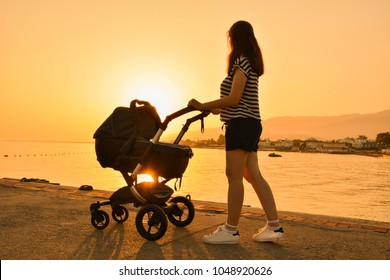 Silhouette mother walking with baby carriage near sea on holiday. sunset is seem on background.