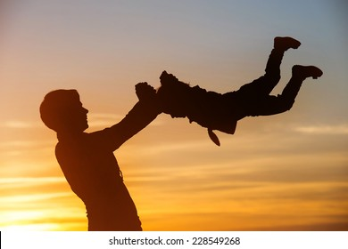 Silhouette of mother which turns her child against a sunset
