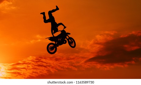 SILHOUETTE: Motocross rider riding fmx motorbike, jumping big air kicker performing extreme stunt. Professional biker jumps no footer knack knack trick over golden sunset sky above trees
