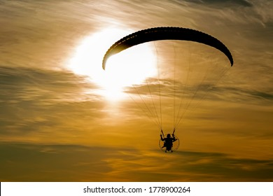 The silhouette of motoparaplane flying against the backdrop of the setting sun, painting the sky and clouds in gold color. See only a silhouette of the wing of the glider in the solar glare.