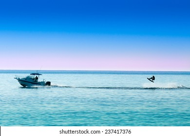 silhouette of motor boat and wakeboarder jumping crazy trick